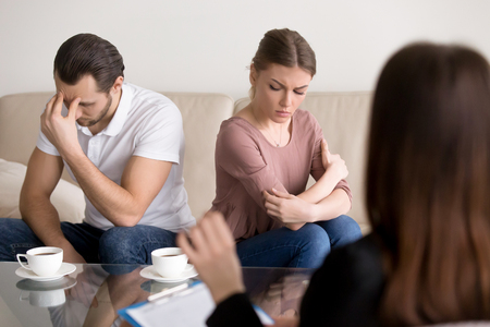 Trusted family relationships expert working with young couple after quarrel not talking to each other, helping to understand and find compromise, repeated fights, conflicts, marriage therapy guidance Stock Photo