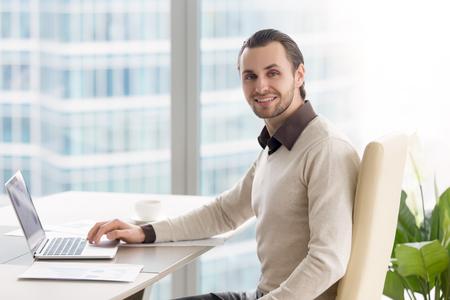 사무실 책상에 앉아 잘 생긴 자신감 젊은 사업가의 초상화. 노트북 및 그래프 직장, 성공적인 관리자가 카메라를 찾고 작업 행복 한 집행자 미소