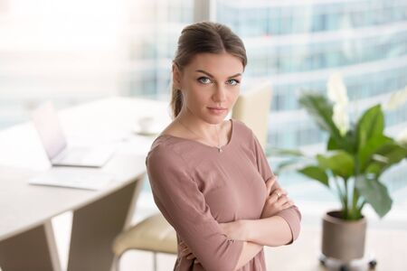 careerist: Portrait of confident young ceo businesswoman standing with arms crossed at office interior, looking at camera. Ambitious careerist, promising junior specialist, administration and management headshot