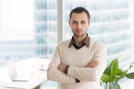 Portrait of young businessman standing in office with arms crossed. Ambitious successful entrepreneur, small business owner or company director posing looking at camera with serious facial expression Stock Photo