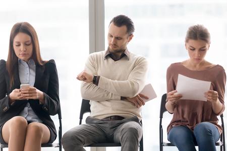 Mensen uit het bedrijfsleven zitten in de rij, vervelend lang wachten, ontmoeting start vertraging, iemand is laat, vervelen, geërgerd ontevreden man kijken polshorloge, wacht in de rij voor interview concept Stockfoto - 77523771