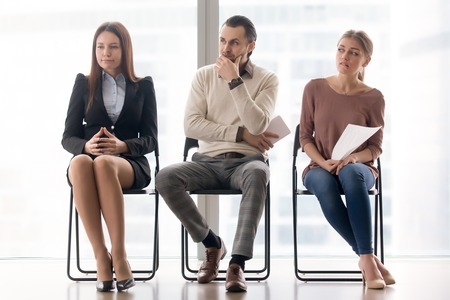 Drie sollicitanten die voorbereidingen treffen voor een sollicitatiegesprek, een audiëntieresultaat in afwachting hebben, zich ongerust en gestresst voelen, in de wachtkamer zitten, lijden aan een gebrek aan zelfvertrouwen, spanning in de lucht Stockfoto - 77523770