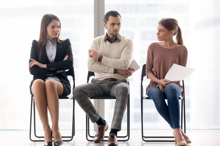 Male and female ambitious job seekers waiting for interview, looking at each other with hate and dislike, feeling jealous envious, rivalry and internal competition, get position and sidestep rivals Stock Photo