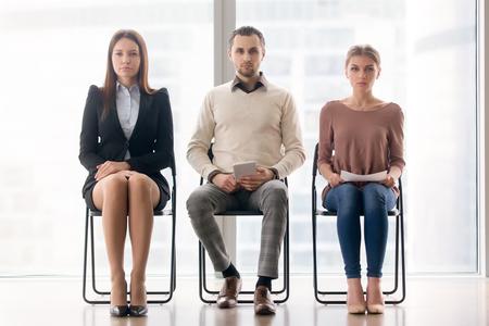 集中と緊張を感じ、面接の順番を待っている候補者、カメラを見て行で椅子に座っている野心的な自信を持っているビジネスマンのグループ。ジョ