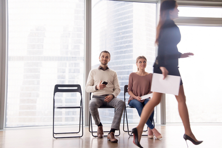 Unhappy attractive businesswoman walking by male and female job candidates sitting on chairs, gazing at her and smiling, gloating over unfortunate competitor, beating rival, competing for position Stock Photo