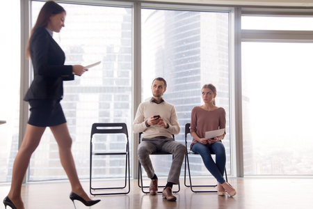 Happy hired woman walking in the room, got a job, being promoted to the post while her colleagues or other applicants looking at businesswoman with envy and hate, feeling winner and loser Stock Photo