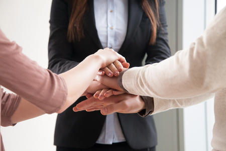 teambuilding: Close up of three people joining hands together, starting joint business, common goal, successful team building, motivated enthusiastic co-workers starting work on project, running company together Stock Photo