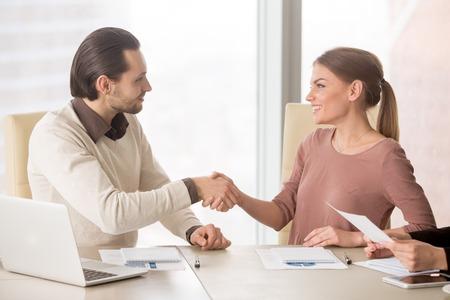 Lachende zakenvrouw handshaking met jonge mannelijke collega, introduceren zich voor de vergadering van de vergadering, start teamwork on project, nieuwe leden van team handen schudden kennis maken Stockfoto