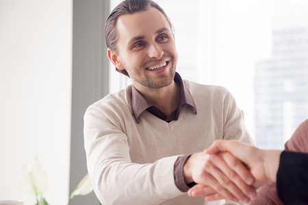Portret van vrolijke knappe jonge zakenman schudden vrouwelijke hand aan het ontmoeten, leuk om u te ontmoeten, zakenpartners maken succesvolle deal, huren professionele, kennis maken met een nieuwe collega Stockfoto