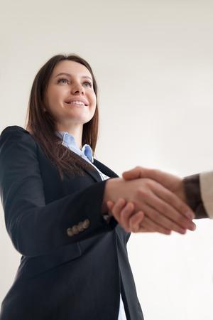 Mooie glimlachende succesvolle zakenvrouw schudden mannelijke hand, manager HR vriendelijke werkzoeker, vrouwelijke executive kennis maken met nieuwe manager, leuk om je te ontmoeten, verticale weergave van onder