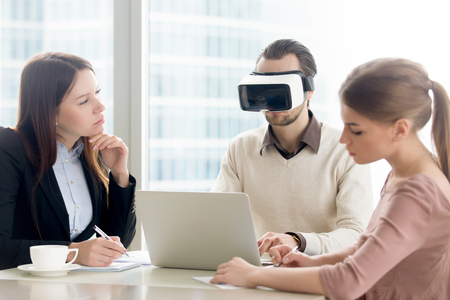 Businessman wearing vr headset for laptop at business meeting. Virtual development business team working on augmented reality improvement, future computer technology for business concept Stock Photo