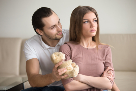 Guilty boyfriend asking for forgiveness, presenting offended girlfriend a teddy bear toy, lady looking proud sitting with arms crossed not going to take gift. Reclaim a fault, apology not accepted Stock Photo