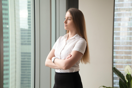 Beautiful woman in formal wear standing with arms crossed and looking in window. Successful businesswoman looking into future with confidence. Ambitious female entrepreneur thinking about perspectives Stock Photo