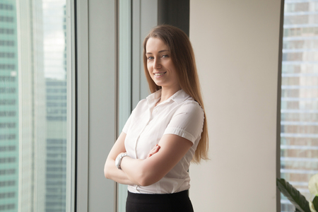 Confident businesswoman enjoys success. Happy woman standing in office with arms crossed, looking at camera. Smiling ambitious female entrepreneur thinking about business, feeling positive. Portrait