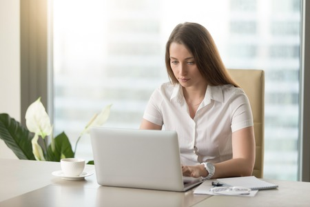 Diligent female office worker doing everyday work routine. Attentive woman sitting at desk and looking at laptop screen. Young businesswoman mailing with colleagues. Entrepreneur working at workplace