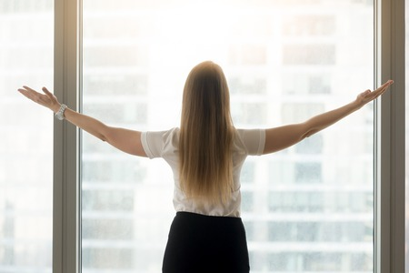 Woman in formal wear spreading arms while standing near the window with cityscape outside. Businesswoman enjoying success, feels inspiration and happiness. Female entrepreneur welcomes the new day