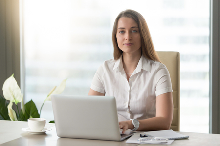 Portrait of confident businesswoman sitting at desk in office and working on laptop. Attractive woman typing on computer and looking at camera. Female office worker doing daily work with pleasure Stock Photo