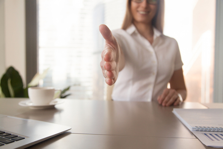 Close up image of reached out for handshake womans hand. Female entrepreneur offering handshake while sitting at work desk. Businesswoman welcomes partners on business meeting. Positive cooperation Banco de Imagens