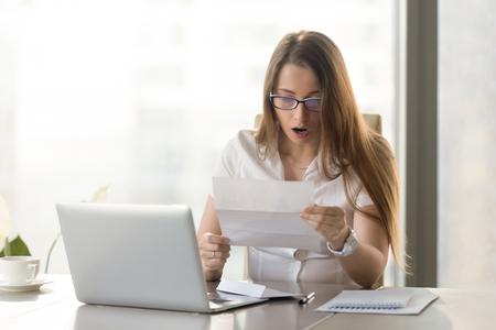 De verraste jonge brief van de onderneemsterlezing bij het bureau voor laptop. De vrouw voelt zich geschrokken na het ontvangen van onverwacht nieuws in een geschreven bericht. Vrouwelijke ondernemer houdt bericht over leningsschuld