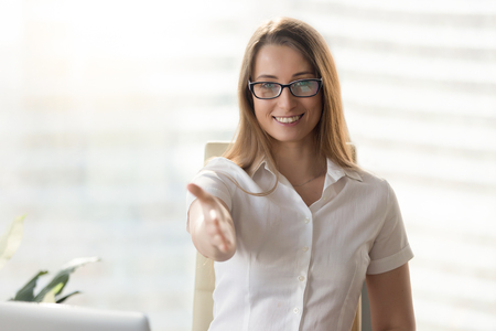 Confident businesswoman reaching out hand for handshake while sitting in office. Female entrepreneur enjoys great agreement. Friendly woman congratulates new partners. Good deal or contract concept