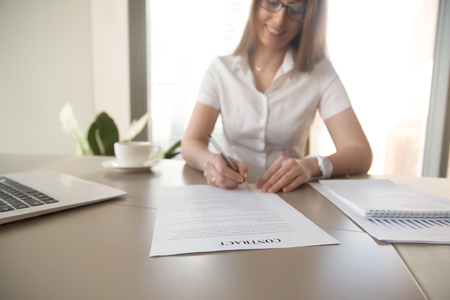 accepts: Smiling businesswoman signs contract on desk. Female entrepreneur puts signature on official agreement. Profitable deal concept. Business partner accepts conditions. Focus on contract, close up