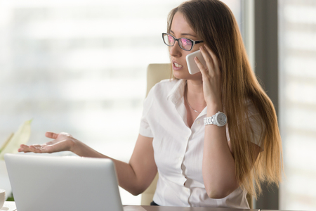 Serious businesswoman talking on cellphone at laptop desk. Entrepreneur arguing with opponent. Office worker solves problem by phone. Woman explains task for colleague, contacts customer service team