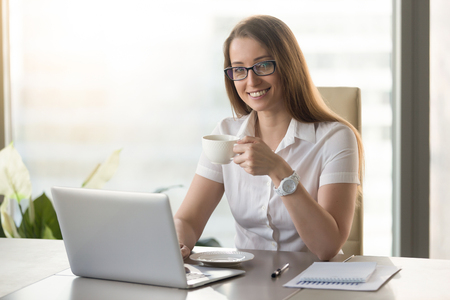 Businesswoman relaxing with cup of aromatic coffee. Smiling confident girl sitting at the desk with mug of hot tea in hand. Short break at the middle of hard working day concept.