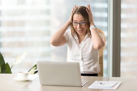 机にノート パソコンの画面を見ながら叫んで押し手で持っていたで終了した実業家。女性は、電子メール上の非常に気持が良い驚きを取得します。ニュースのためにショックを受けた女性起業家なる狂気 写真素材 - 77767882