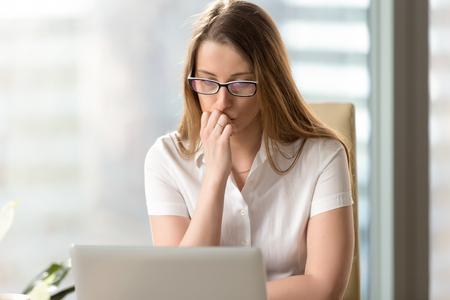 Jovem mulher que olha atentamente na tela do portátil no escritório. Mulher de negócios ponderando a decisão do problema. Empreendedor feminino pondera uma resposta no e-mail. Trabalhador de escritório pensativo duvida sobre resultados Foto de archivo