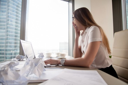 Female office worker yawning at desk covered crumpled papers. Businesswoman feeling lack of energy, sleep deprived after hard paperwork. Woman entrepreneur tired after work at night on urgent project