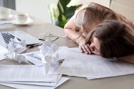 Tired woman sleeping at workplace covered crumpled papers. Overworked female entrepreneur give up after hard day and dozing at desk. Stressed businesswoman lying on table with documents under her head