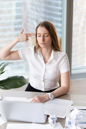Overworked busy businesswoman wants kill herself because of difficult work and fatigue. Tired office worker showing finger gun aimed at the head. Exhausted female entrepreneur with suicidal thoughts