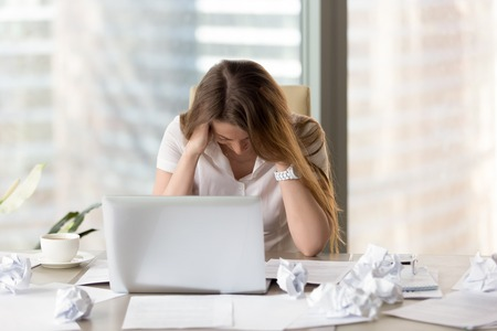 Empresaria desesperada que se sienta en el escritorio con la computadora portátil y el papel arrugado. La oficinista sufre debido a demasiado desorden en sus pensamientos. Stressed woman entrepreneur feeling creatividad crisis Foto de archivo - 77768176