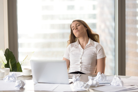 Tired employee sleeping in front of laptop at the desk covered crumbled papers. Overworked female entrepreneur resting at workplace. Businesswoman in knockout after too much exhausting work on project Stock Photo