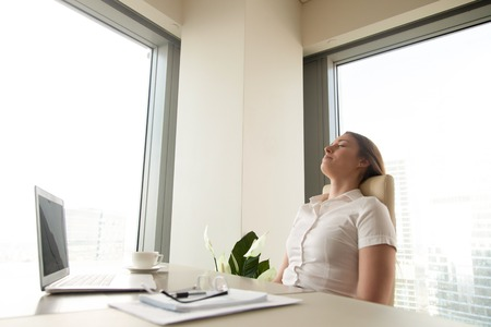 Businesswoman has deep relaxation at workplace. Relaxed woman sitting with closed eyes at the desk with laptop in office. Short recovering sleep on work. Minute break for increasing productivity Reklamní fotografie