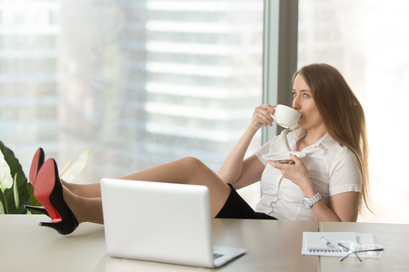 Businesswoman drinking coffee with legs on desk. Girl resting at the desk with cup of tea. Confident lady takes a break at work. Successful female entrepreneur relaxing after productive day in office