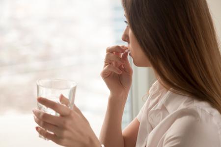 Jovem mulher toma pílula redonda branca com um copo de água na mão. Salientou a fêmea olhando pela janela e bebendo remédios antidepressivos sedados. Mulher se sente deprimida, tomando drogas. Medicamentos no trabalho