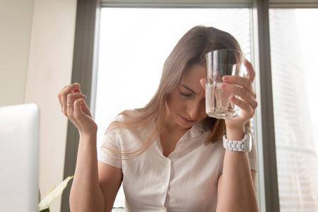 Onderneemster die aan hoofdpijn op het werk lijdt. Benadrukt jonge vrouw zet glas water op het voorhoofd en pil in de hand te houden. Vrouw die plotselinge ziekte op het werk voelt. Verslaving na medicijnen