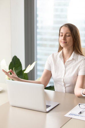 Beautiful businesswoman meditating at the table in office. Calm girl relaxing at her workplace with spiritual practices. Female entrepreneur focusing on positive result of work Stockfoto