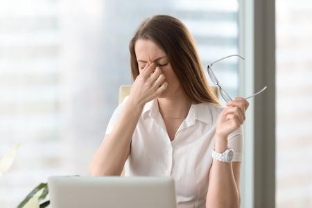 Empresaria cansada celebración de gafas y masaje nariz puente. Sensación de incomodidad de la muchacha de gafas de largo uso en el lugar de trabajo. Trabajadora de oficina exhausta se reúne para completar el trabajo