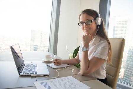 Mujer sentada frente a la computadora portátil con auriculares en la cabeza y escribir en el cuaderno. Las mujeres aumentan el vocabulario de lenguas extranjeras con cursos en línea. Emprendedor se comunica con colegas en Internet