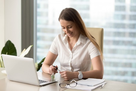 Smiling businesswoman painting nails in office. Female entrepreneur takes short break for refresh her manicure. Pretty girl sitting at the desk in front of laptop and applying varnish on fingernails