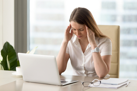Businesswoman under terrible physical tension at work. Female entrepreneur with head ache sitting at desk in front of laptop, massaging temples. Stressed young girl on the edge of a nervous breakdown Stock Photo