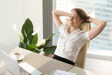 Joyed businesswoman keeping eyes closed while sitting at the desk with hands behind head. Happy lady leaning back in chair and relaxing with cup of coffee. Having positive feelings about work concept