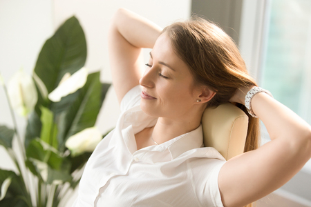 Beautiful woman dreaming with closed eyes in office chair. Businesswoman feels relaxed after busy working day. Female leaning back in chair with hands behind head. Satisfied girl resting at workplace