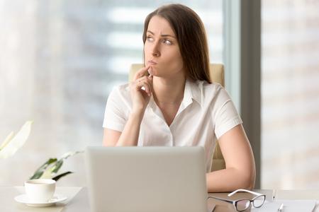 Vrouw die met peinzende gelaatsuitdrukking opzij terwijl het zitten op het werk kijkt. Onzekere onderneemster die over moeilijke vraag denkt. Vrouwelijke beambte betwijfelde wegens onzekere situatie