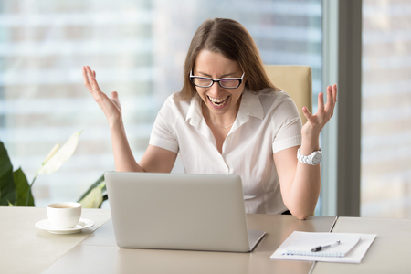 Shocked female hysterically screaming because of computer critical error. Stressed mad businesswoman in rage after application glitch on her laptop. Complete loss of important information through bug