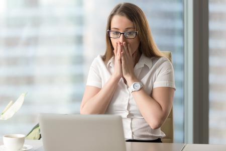Überrascht geschäftsfrau Blick auf Laptop-Bildschirm. Hübsches Mädchen plötzlich mit E-Mail oder Nachrichten im Internet verwirrt. Junge weibliche Büroangestellte sieht schockiert nach Computer kritischen Fehler