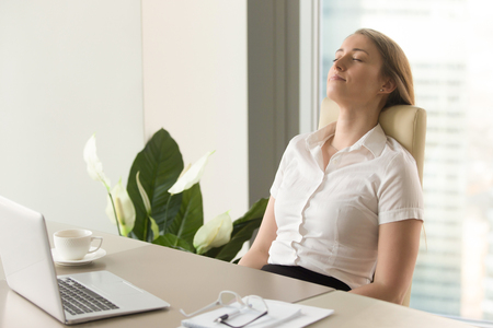 Businesswoman takes short time-out in office work. Beautiful girl lying relaxed on back chair. Female entrepreneur resting at workplace. Comfortable office furniture for long work in sitting position Фото со стока