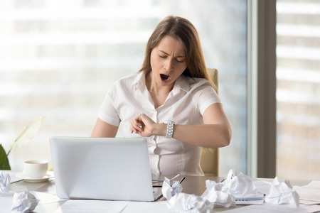Young businesswoman yawning while working on laptop in office. Sleepy female entrepreneur looking on wristwatch. Tired office worker feels lack of sleep because of hard and long work with documents